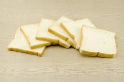 Geschnittenes Brot auf braunem Holz Stockfotografie