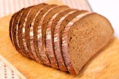 Geschnittenes Brot auf einem hölzernen Ausschnittvorstand Lizenzfreie Stockfotografie