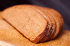 Geschnittenes Brot auf einem hölzernen Ausschnittvorstand Stockbild