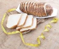 Geschnittenes Brot und Maßband Stockfotografie