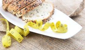 Geschnittenes Brot und Maßband Stockbild