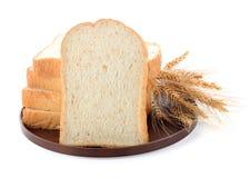Geschnittenes Brot und Weizen auf hölzernem Brett lizenzfreies stockfoto