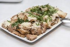 Geschnittenes Fleisch mit Käse und rucola diente auf einer Platte Stockfotos