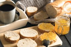 Geschnittenes französisches Brot mit Pfirsichstau und -kaffee Lizenzfreie Stockfotografie