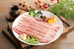 Geschnittenes frisches Schweinefleisch auf weißer Platte mit Kräutern und Paprika Stockbild