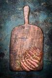 Geschnittenes gegrilltes Rindfleischgrillsteak auf hölzernem Schneidebrett auf rustikalem Hintergrund Stockbild