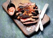 Geschnittenes gegrilltes Rindfleischsteak mit Messer und Gabel für Fleisch auf hölzernem Schneidebrett Stockfotografie
