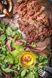 Geschnittenes gegrilltes Steak diente mit grünem Salat, Barbecue-Soße und Tischbesteck Stockfotografie