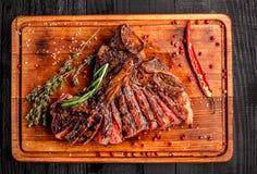 Geschnittenes halb gares gegrilltes Steak auf rustikalem Schneidebrett mit Rosmarin und Gewürzen, dunkler rustikaler hölzerner Hi Lizenzfreie Stockfotografie