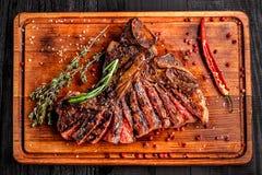 Geschnittenes halb gares gegrilltes Steak auf rustikalem Schneidebrett mit Rosmarin und Gewürzen, dunkler rustikaler hölzerner Hi Lizenzfreies Stockbild