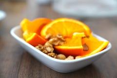Geschnittenes Orange und nuts zusammen in einer Schüssel lizenzfreies stockfoto