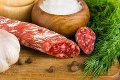 Geschnittenes salame auf Schneidebrett, mit Dill, Pfeffer, Salz Stockfoto