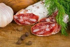 Geschnittenes salame auf Schneidebrett, mit Dill und Pfeffer Stockfoto