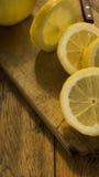 Geschnittenes und ganzes hölzernes hackendes Brett der Zitronen O eine Tabelle Lizenzfreies Stockbild