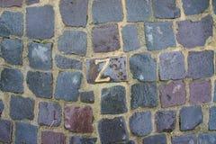 Geschnitzte Buchstaben in den grauen Pflastersteinen Stockfotos