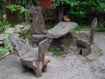 Geschnitzte Gartenmöbel hergestellt von den Baumstämmen stockfotografie
