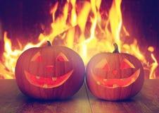 Geschnitzte Halloween-Kürbise auf Tabelle über Feuer Lizenzfreies Stockfoto