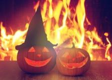Geschnitzte Halloween-Kürbise auf Tabelle über Feuer Stockbild