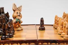 Geschnitzte Hasen auf dem Schachbrett Stockfotografie