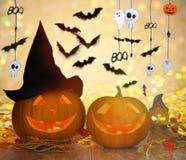 Geschnitzte Kürbise im Hexenhut und in Halloween-Girlande Stockbild