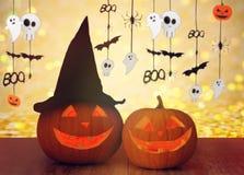 Geschnitzte Kürbise im Hexenhut und in Halloween-Girlande Stockfotos