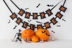 Geschnitzte Kürbise mit Süßigkeiten und Halloween-Girlande Stockfotos
