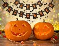 Geschnitzte Kürbise und glückliche Halloween-Girlande Stockfotos