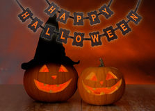 Geschnitzte Kürbise und glückliche Halloween-Girlande Stockbilder