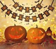 Geschnitzte Kürbise und glückliche Halloween-Girlande Lizenzfreie Stockfotos
