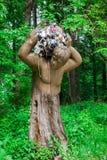 Geschnitzte Statue eines Baums trägt Abfall vom Wald Stockbild