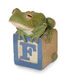 Geschnitzter hölzerner Frosch auf Block des Kindes stockbilder