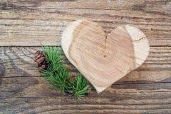 Geschnitztes hölzernes Herz und Lärchenniederlassung mit Kegel auf einem Hintergrund O Stockbild