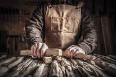 Geschnitztes Holz in den Händen stockbild
