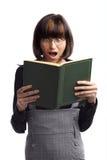 Geschokt donkerbruin schoolmeisje dat in het boek kijkt Stock Foto's