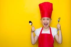Geschokt en verrast meisje die in het kostuum die van een rode chef-kok gillen een lepel en een vork op gele achtergrond met exem stock afbeeldingen