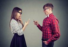 Geschokt jong paar die slimme telefoons met behulp van stock foto's