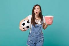 Geschokt jong van de de ventilator lettend op gelijke van de meisjesvoetbal de steun favoriet team met voetbalbal, emmer geïsolee stock foto