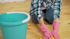 Geschokt vrouwen schoonmakend huis met veel hulpmiddelen Het jonge vermoeide meisje werpt een vod in een emmer stock video