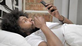Geschokte Afrikaanse Mens die Smartphone in Bed gebruiken stock footage