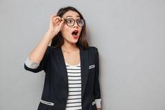 Geschokte bedrijfsvrouw die in oogglazen weg met open mond kijken stock foto