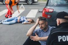 Geschokte bestuurder die aan politieagent na autoongeval spreken Stock Foto's