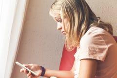 Geschokte blonde tiener met smartphone royalty-vrije stock afbeeldingen