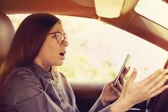 Geschokte die vrouw door mobiele telefoon wordt afgeleid die terwijl het drijven van een auto texting stock fotografie