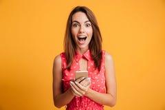 Geschokte donkerbruine vrouw in smartphone van de kledingsholding Royalty-vrije Stock Fotografie