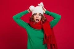 Geschokte donkerbruine vrouw in sweater, grappige hoed en sjaal Royalty-vrije Stock Foto