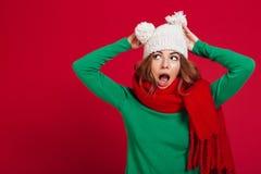 Geschokte donkerbruine vrouw in sweater, grappige hoed en sjaal Stock Afbeelding