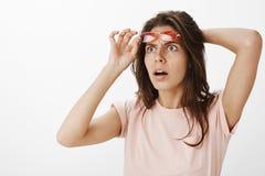 Geschokte en verraste overweldigde aantrekkelijke vrouw die UFO in hemel het nemen van rode zonnebril getuigen die bij hogere lin stock foto's