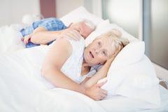 Geschokte hogere vrouwenslaap naast de mens op bed Royalty-vrije Stock Fotografie
