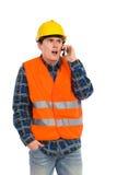 Geschokte ingenieur die celtelefoon met behulp van. Royalty-vrije Stock Afbeeldingen