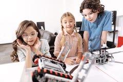 Geschokte jonge geitjes die elektronische robots waarnemen op school Royalty-vrije Stock Foto's